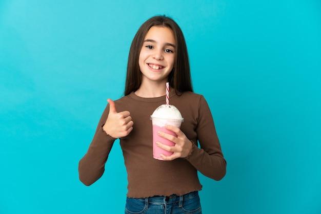 青い背景に分離されたイチゴのミルクセーキと親指を立てるジェスチャーを与える少女