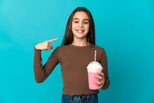 Маленькая девочка с клубничным молочным коктейлем, изолированные на синем фоне, показывает палец вверх жест