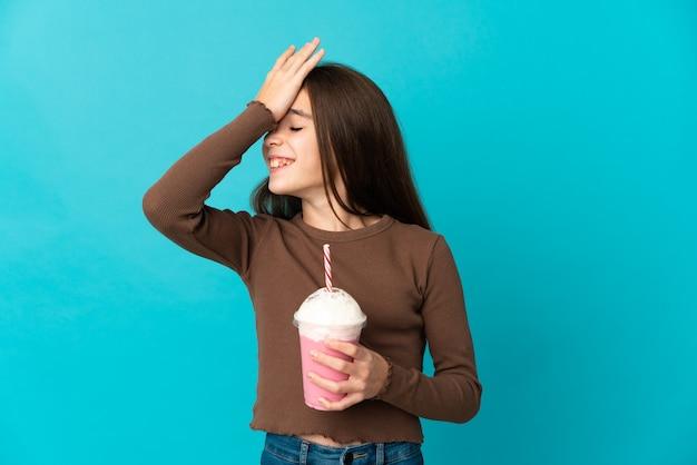 Маленькая девочка с клубничным молочным коктейлем, изолированным на синем фоне, кое-что поняла и намеревается решить