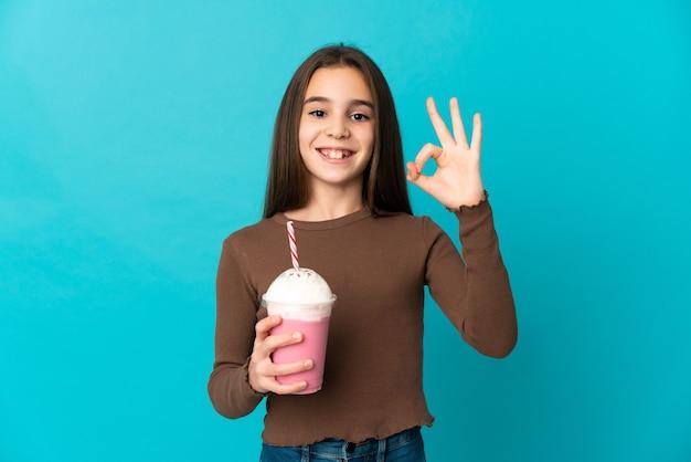 Маленькая девочка с клубничным молочным коктейлем изолирована на синем фоне, показывая пальцами знак ок