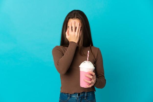 疲れて病気の表情で青い背景に分離されたイチゴミルクセーキの少女