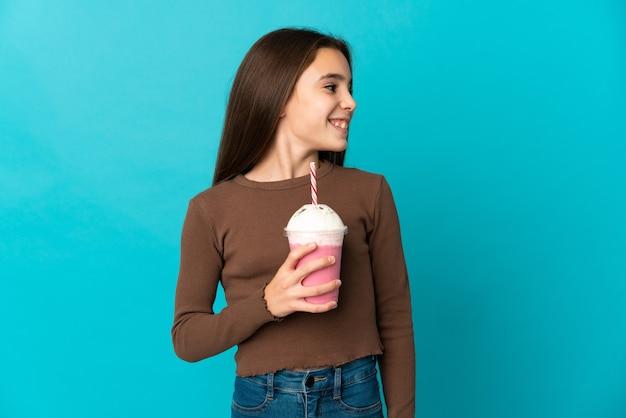 側を見て青い壁に分離されたイチゴのミルクセーキを持つ少女