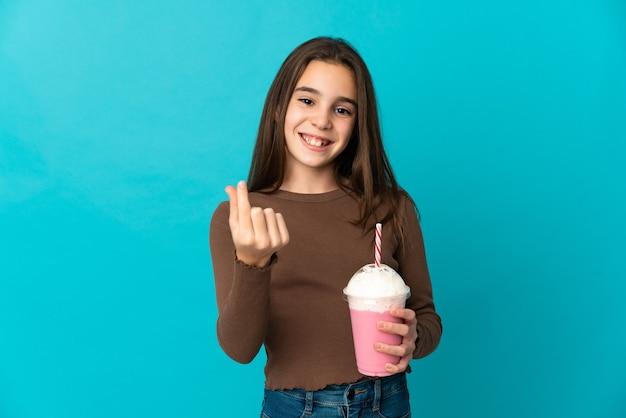 Маленькая девочка с клубничным молочным коктейлем изолирована на синей стене, делая денежный жест