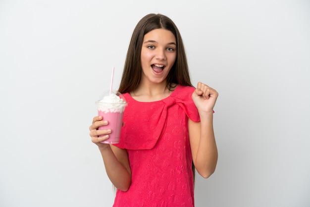 우승자 위치에서 승리를 축하하는 고립 된 흰색 배경 위에 딸기 밀크 쉐이크와 어린 소녀