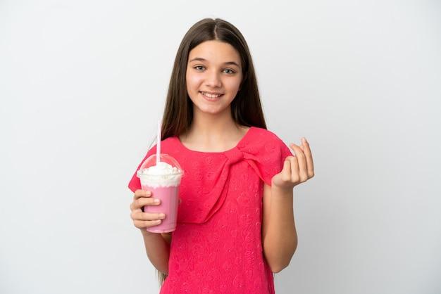 돈 제스처를 만드는 고립 된 흰색 배경 위에 딸기 밀크 쉐이크와 어린 소녀