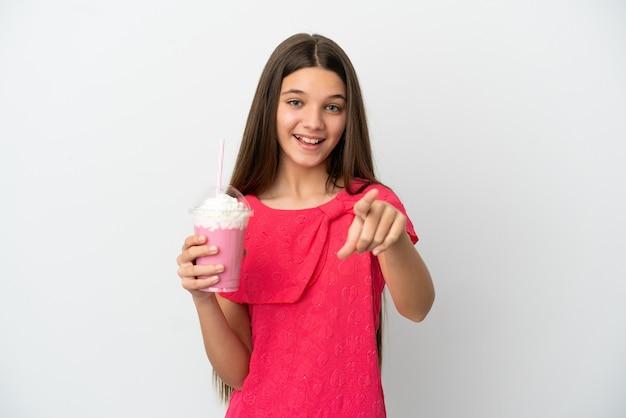 격리된 흰색 배경 위에 딸기 밀크셰이크를 든 어린 소녀가 놀라 앞을 가리키고 있다