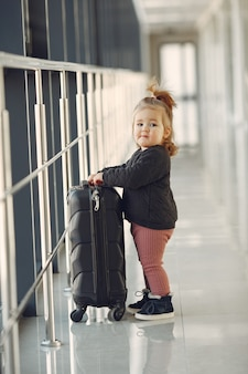 Little girl with a suitcase at the airport