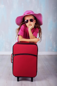 The little girl with a suitcase. the concept of travel and leisure.