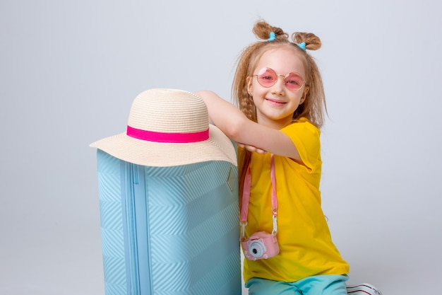 Little girl with a suitcase traveler on a white background