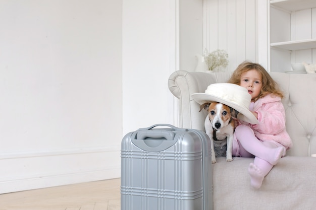 A little girl with suitcases and a dog in interior