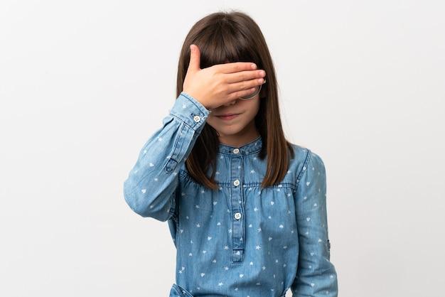 손으로 눈을 덮고 흰색 배경에 고립 된 선글라스와 어린 소녀. 뭔가보고 싶지 않아