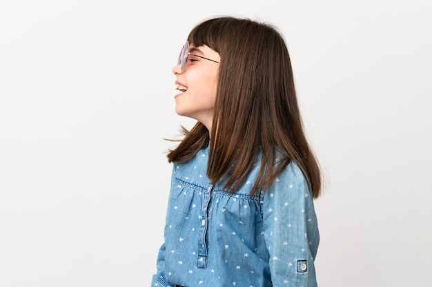 Маленькая девочка в солнцезащитных очках, изолированные на белом фоне, смеясь в боковом положении