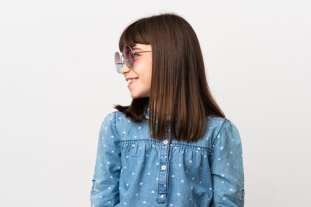 측면을 찾고 흰색 배경에 고립 된 선글라스와 어린 소녀
