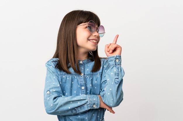 좋은 아이디어를 가리키는 흰색 배경에 고립 된 선글라스와 어린 소녀