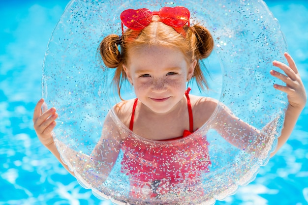 Little girl with a swimming circle in the pool