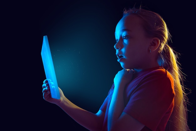 Little girl with tablet in neon light