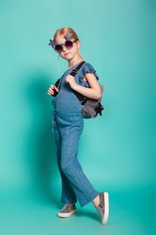 Little girl with a tail in stylish clothes and sunglasses