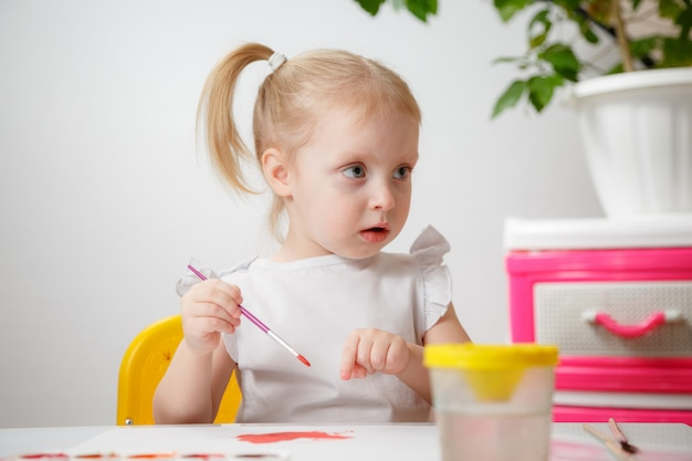 A little girl, with tails on her head, draws watercolors sitting at a table. the child likes to be creative