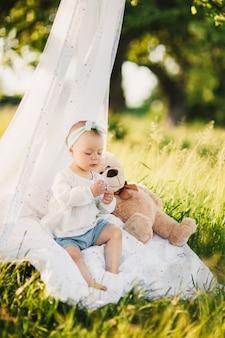 Маленькая девочка с плюшевым мишкой сидит на белом одеяле в летнем солнечном парке.