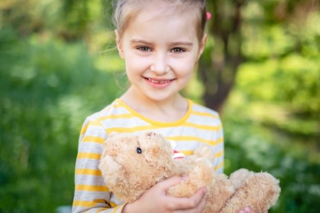 Little girl with teddy bear in park