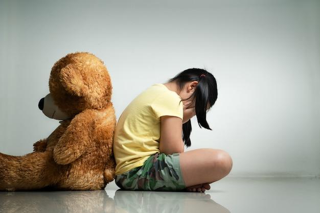 空の部屋で床に座っているテディベアを持つ少女。精神的で落ち込んでいる家族の概念。背面図