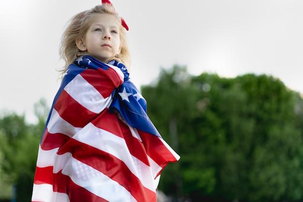 자연에 미국 국기가 달린 어린 소녀, 애국심의 개념, 미국 독립 기념일. 재향 군인의 날 미국.