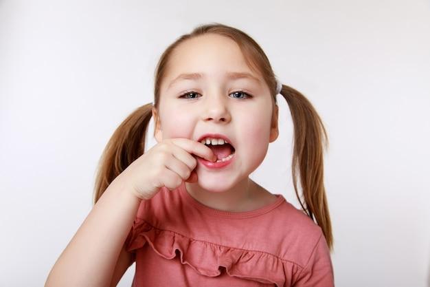 Маленькая девочка с первым качающимся молочным зубом