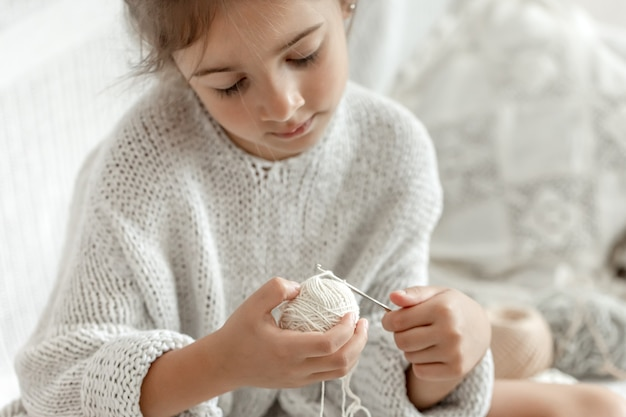 Little girl with threads learns to crochet, home leisure and needlework.