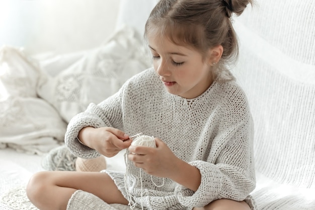 Маленькая девочка с нитками учится вязанию крючком, домашнему отдыху и рукоделию.