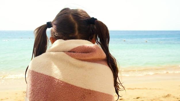 해변에서 수건에 싸인 두 개의 포니테일을 가진 어린 소녀
