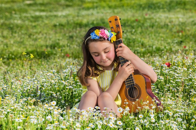 Little girl with ukulele relaxing in summer countryside