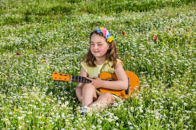 Little girl with ukulele resting in field