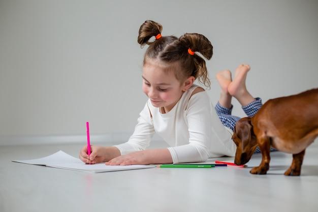 Маленькая девочка с необычной прической лежит на деревянном полу, рисует в альбоме цветными карандашами