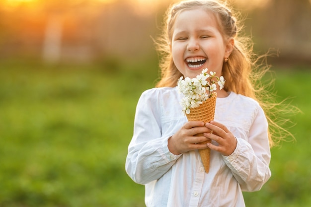 Little girl with waffle cone filled, blooming cherry branches, holding her hand
