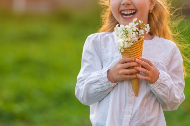 Little girl with waffle cone filled, blooming cherry branches