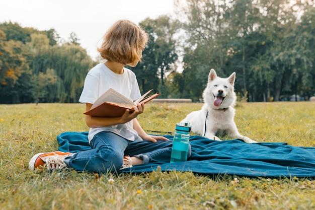 Маленькая девочка с белой собакой хаски в парке