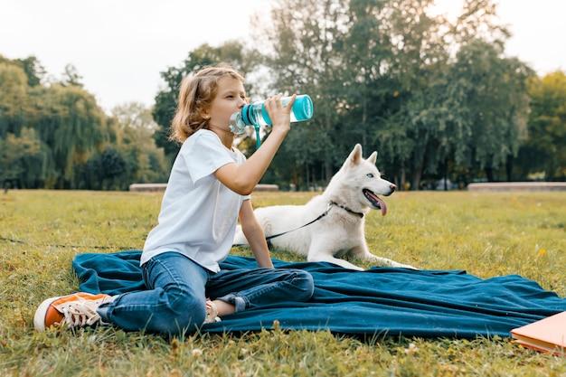 Маленькая девочка с белой собакой в парке, сидя на траве