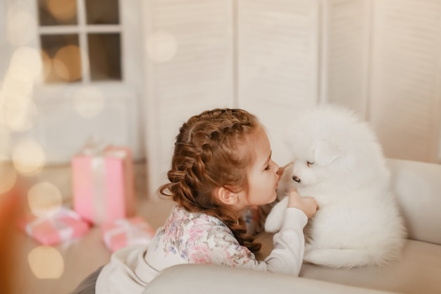 Little girl with white puppies and gift boxes