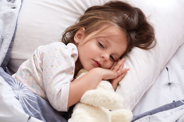 Little girl with white soft dog relaxing in bed, hugging her toy, keeps eyes opened lying on pillow under warm blanket, charming female kid with dark hair wearing white pajama.