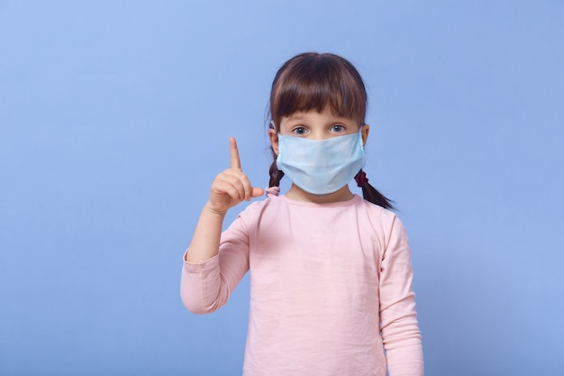 人差し指を上に向けてカジュアルなバラのシャツと防護マスクを身に着けている、大きく開いた目を持つ少女
