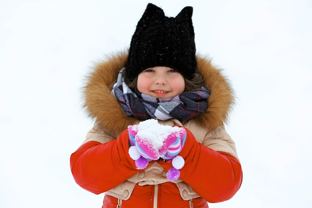Little girl with winter clothes holding snow in hands outdoor, close up