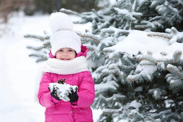 눈 덮인 공원 야외에서 손에 눈을 들고 겨울 옷을 입은 어린 소녀