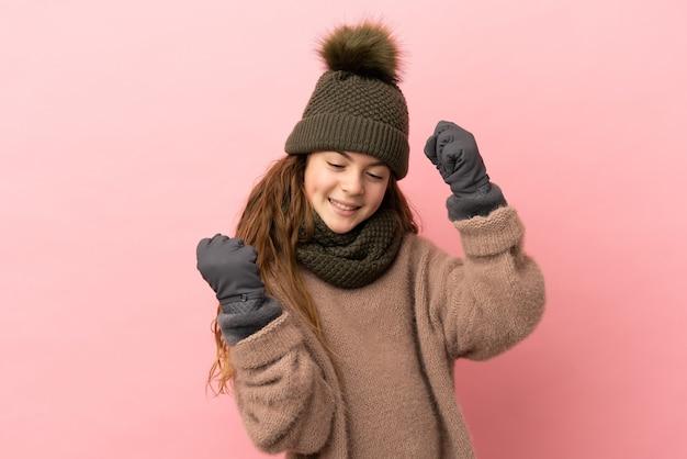 승리를 축하하는 분홍색 배경에 고립 된 겨울 모자와 어린 소녀
