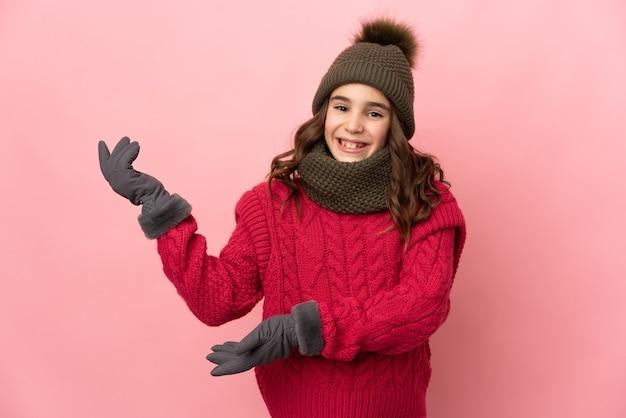 ピンクの背景で隔離の冬の帽子を持つ少女は、来るように招待するために手を横に伸ばします