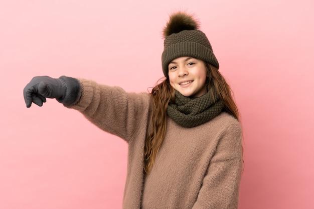 ピンクの背景に分離された冬の帽子の少女