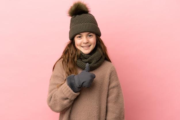 親指を立てるジェスチャーを与えるピンクの背景に分離された冬の帽子を持つ少女