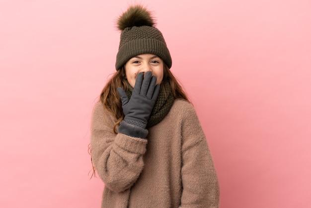 Маленькая девочка в зимней шапке, изолированные на розовом фоне, счастливая и улыбающаяся, прикрывая рот рукой