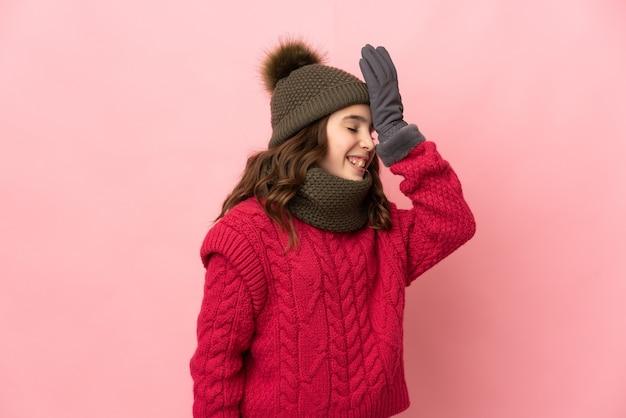 Маленькая девочка в зимней шапке, изолированной на розовом фоне, кое-что поняла и намеревается найти решение