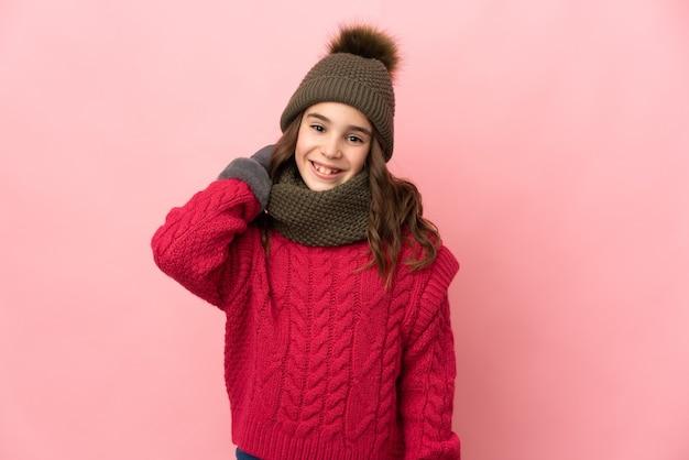 Маленькая девочка в зимней шапке, изолированные на розовом фоне смеясь