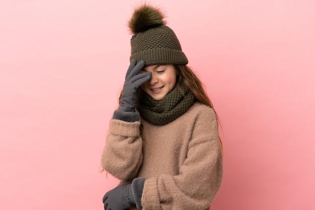 분홍색 배경에 격리된 겨울 모자를 쓴 어린 소녀가 웃고 있습니다.